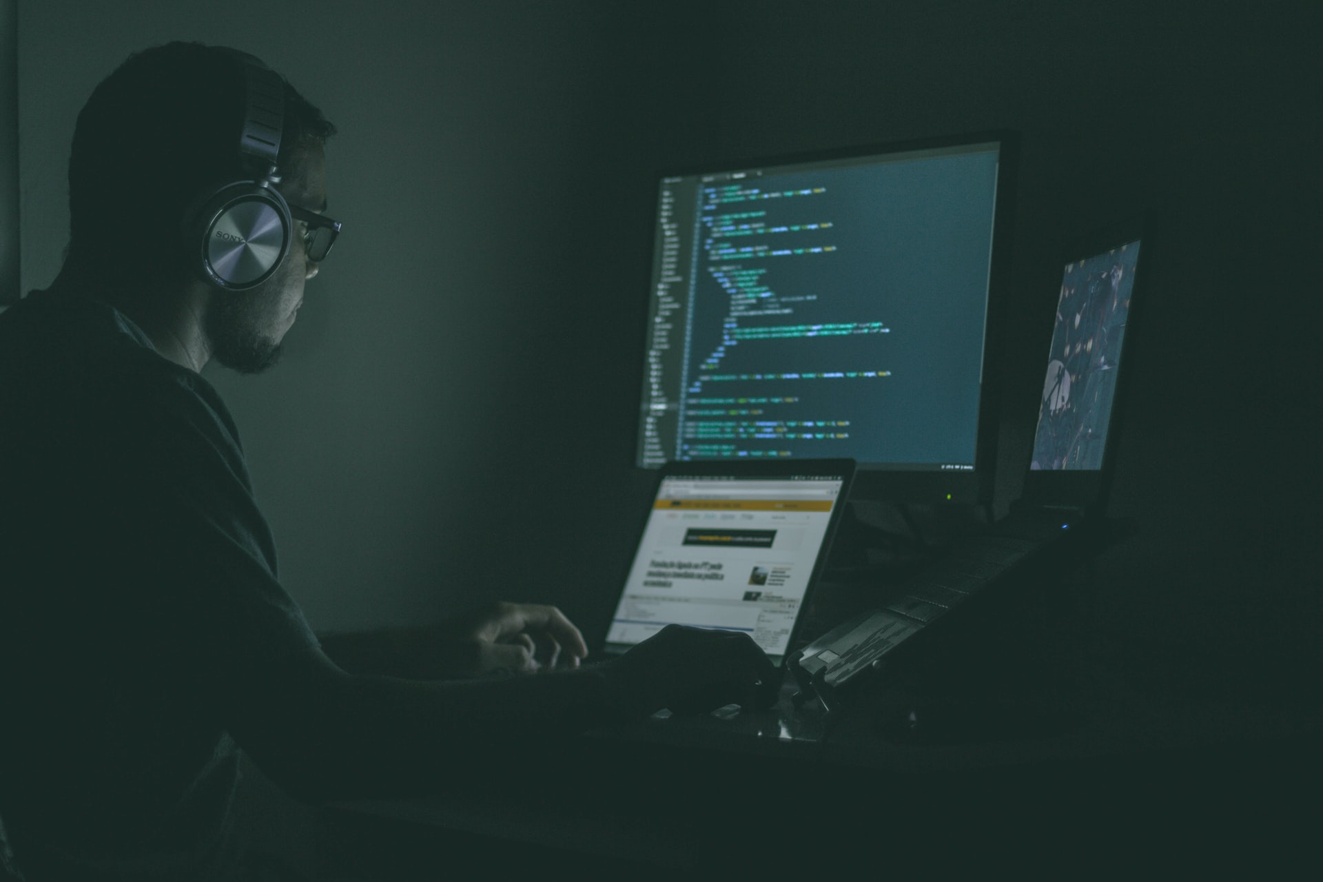 White man with headphones sitting in the dark looking at a computer screen with code text on it.